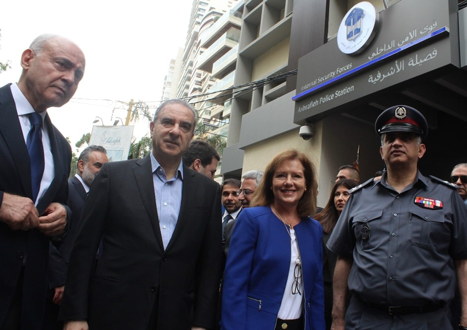 Two men, woman and officer standing before a building